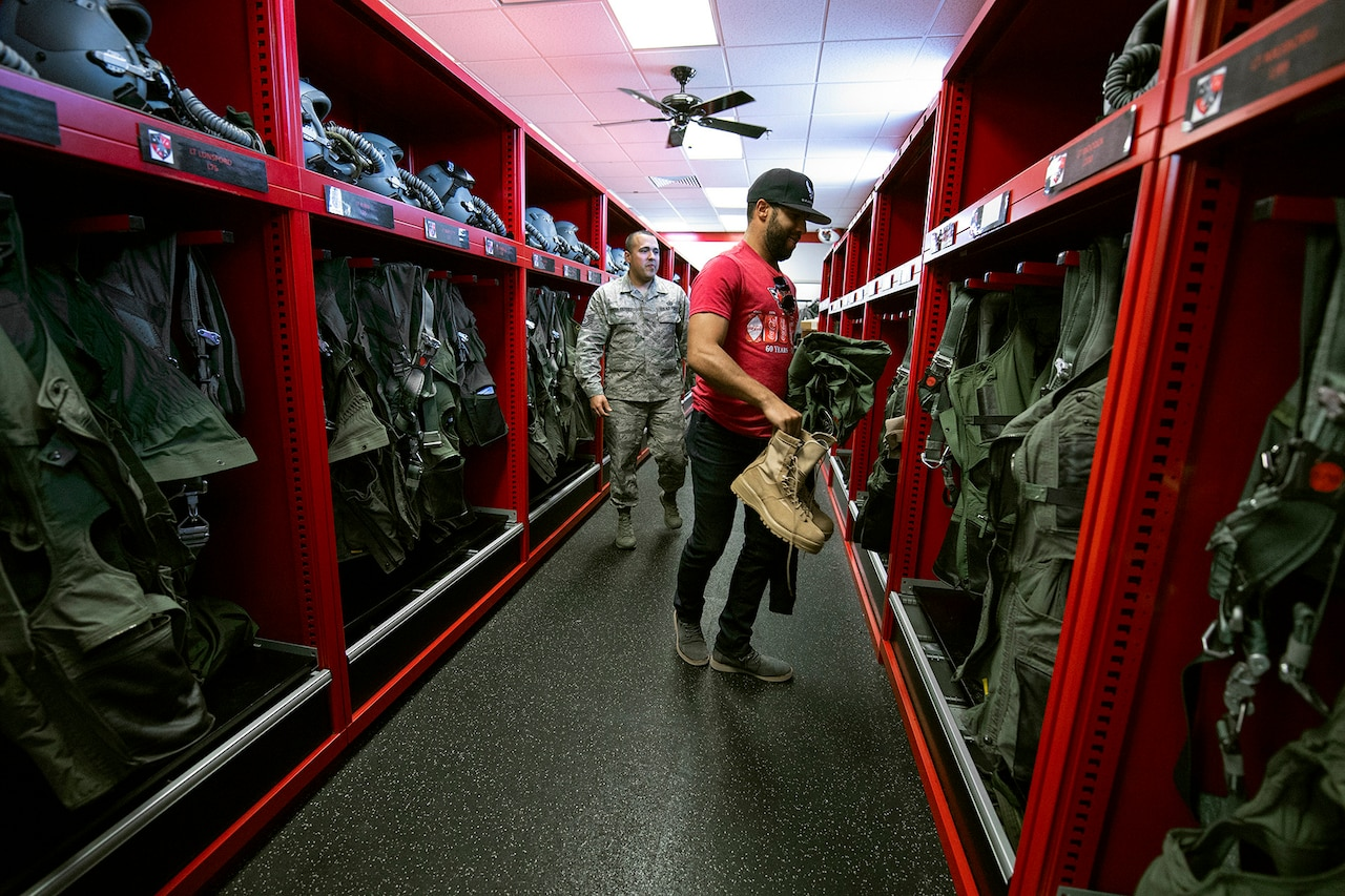 An airman shows a civilian what gear to grab.