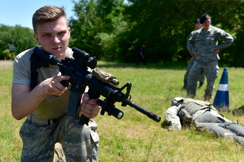 A man wearing ABUs holds a weapon.