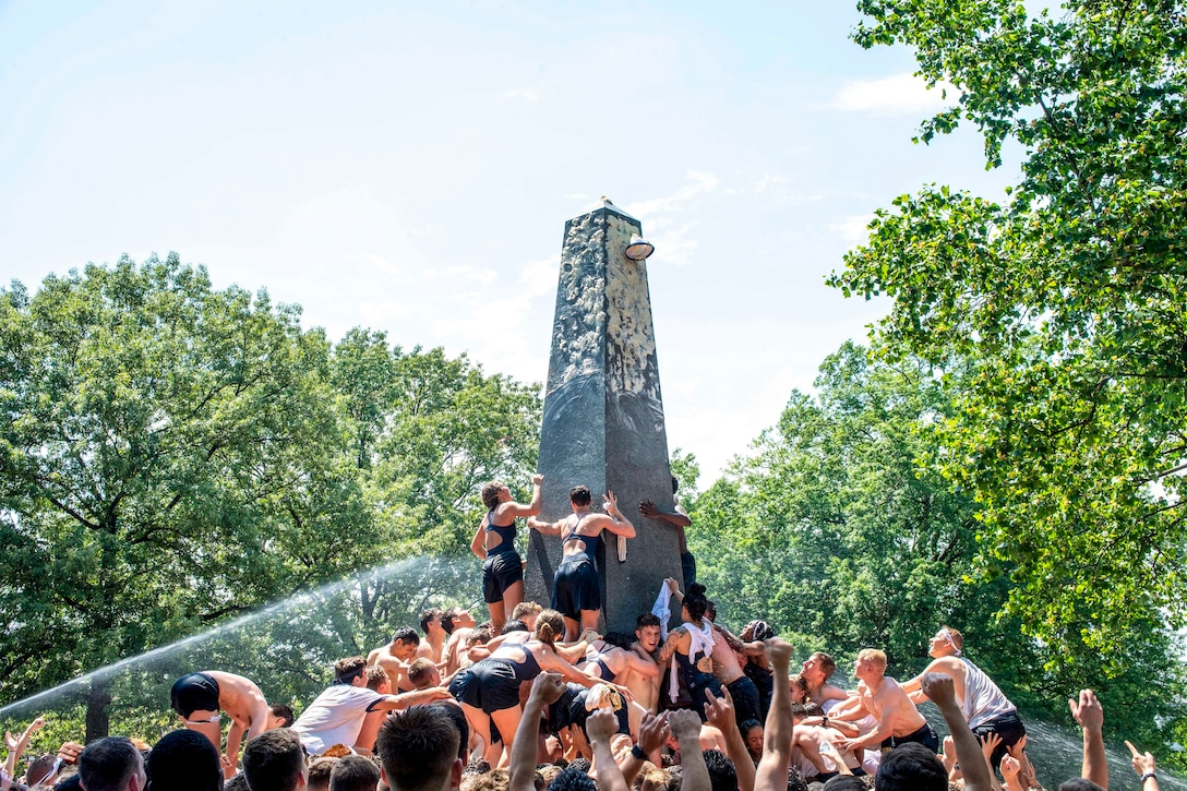 Students in  swimsuits climb on top of one another toward the top of an obelisk.