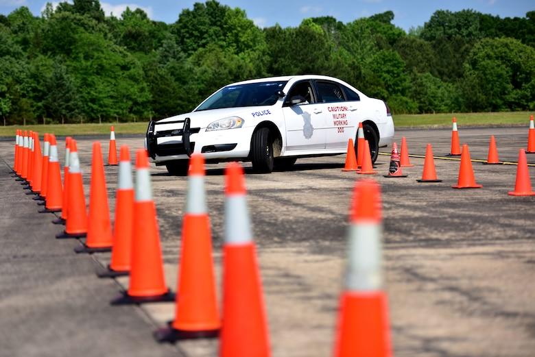 A police car drives through cones.