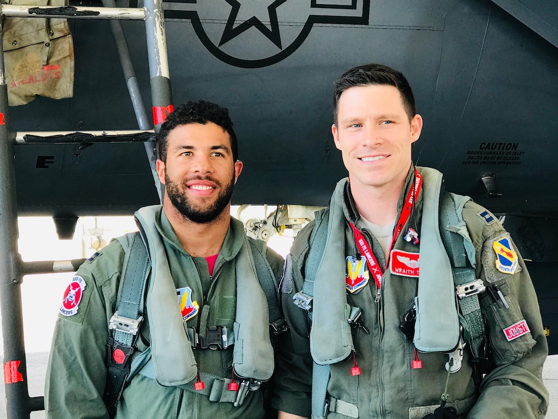 Two men in flight suits stand beside each other.