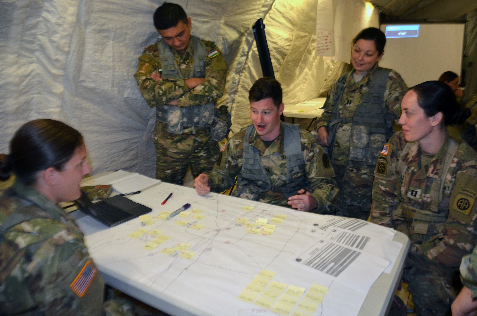 Army Medical Department Center & School, Health Readiness Center of Excellence students participate in a field training exercise for the Captains Career Course at Joint Base San Antonio-Camp Bullis May 7. Sitting clockwise at the table are Capts. Mike Bird, Maureen Mulholland and Kirby Leininger, who are looking at a map of Houston in a scenario in which a hurricane has made landfall on the city. During the exercise, the students put together a support operations plan for a medical battalion that is supporting civil authorities responding to the hurricane. Students in the Captains Career Course undergo nine weeks of training that includes classroom and hands-on training about the Military Decision Making Process, Army Health Systems Support and Force Health Protection doctrine, unit training management, leadership skills and staff officer functions.