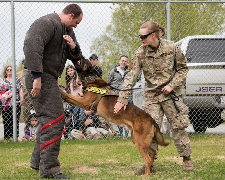 U.S. Air Force Staff Sgt. Melissa Udulutch, a 673d Security Forces Squadron Military Working Dog handler and MWD Chase, provide a demonstration at Joint Base Elmendorf-Richardson, Alaska, May 16, 2019. In commemoration of Police Week, multiple demonstrations and activities were organized to highlight defender-style training and work conduct which included a defender family day tour.