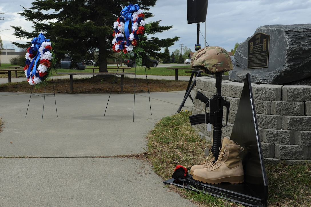 Wreaths placed by 673d Security Forces Squadron personnel sit near a defender memorial during a Final Guard Mount Memorial Service at Joint Base Elmendorf-Richardson, Alaska, May 17, 2019. The memorial service was conducted to honor defenders during Police Week and those who have paid the ultimate sacrifice.