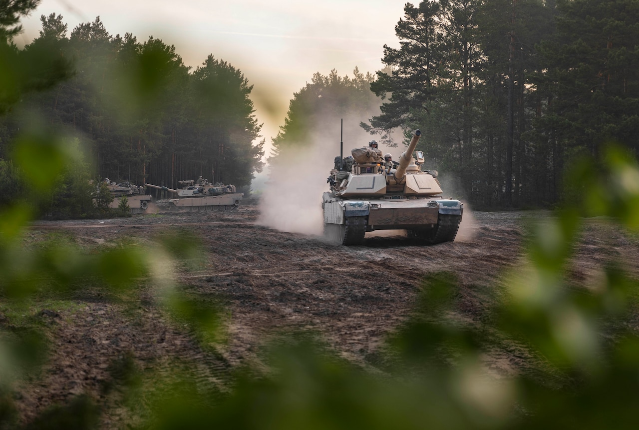 A tank with several soldiers aboard kicks up dust as it rolls down a path lined with trees.