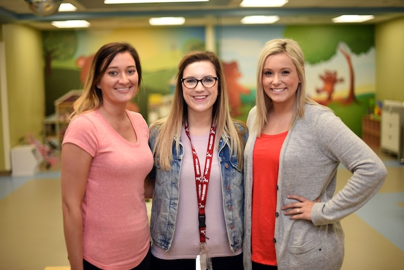 Nicole Hall, Teddy's Child Watch manager, center, joins Cheyenne Dion, right, and Ashley Winston, left, both Teddy's Child Watch volunteers, in posing for a photo inside the care center's playroom May 21, 2019, at Travis Air Force Base, California. The mission of Teddy's Child Watch is to provide service members the free option of dropping off their children while attending important medical appointments at the base's David Grant USAF Medical Center. (U.S. Air Force photo by Senior Airman Christian Conrad)