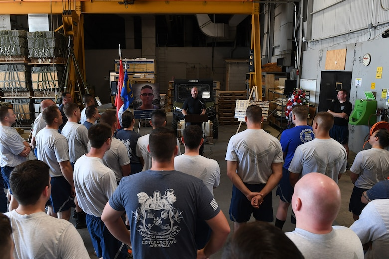 Airmen stand in front of a man speaking.