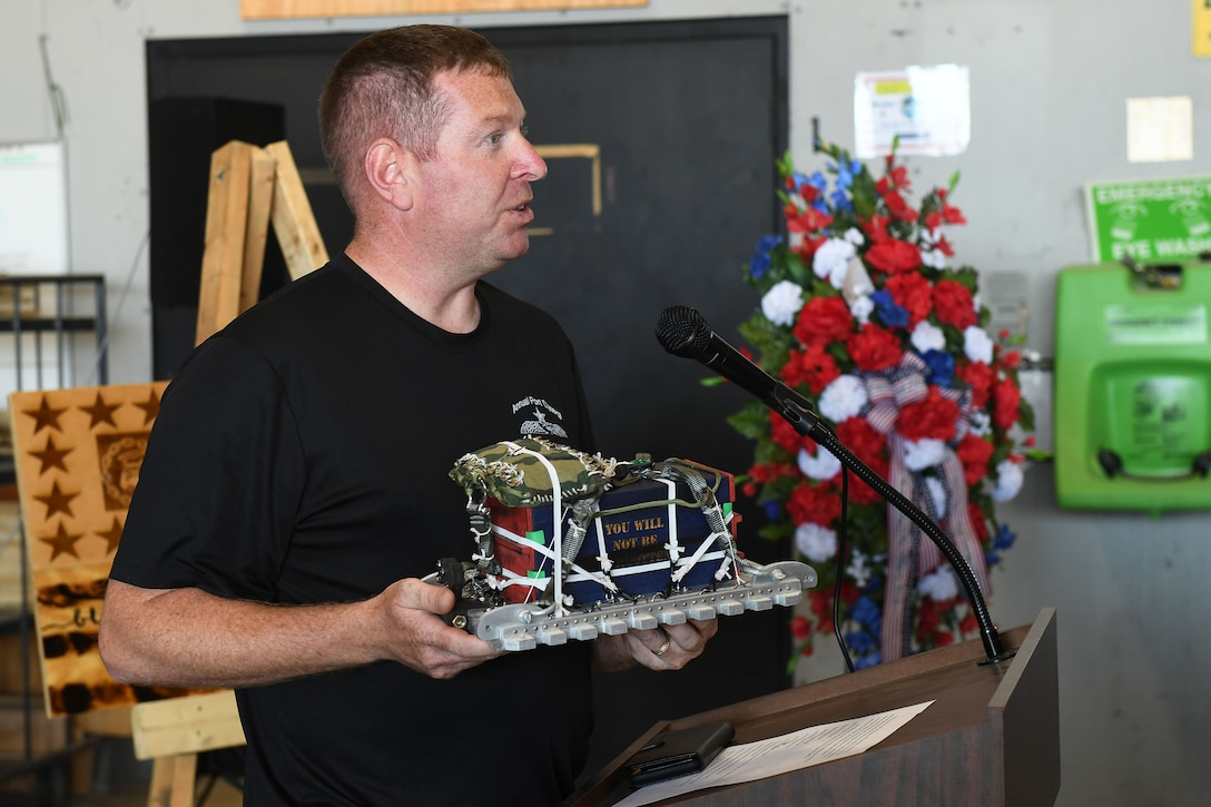 A man holds a miniature model of a heavy aerial delivery cargo unit.