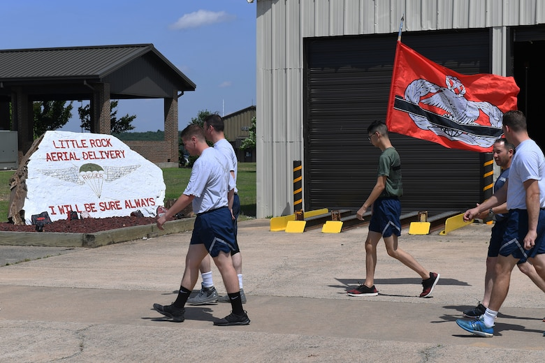 A group of Airmen walk from the left to the right of the frame.