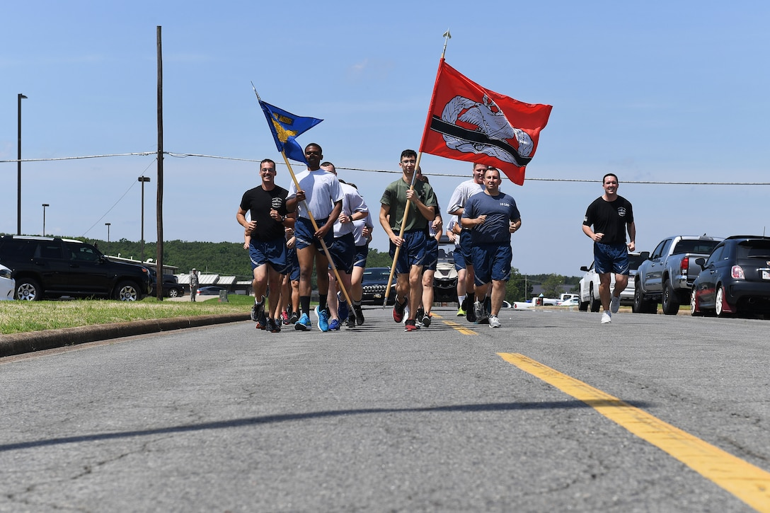 Men and women run down a road in formation.