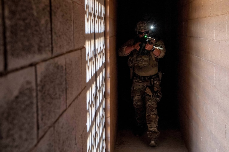 A sailor wearing a helmet with an attached light emerges from a dark hallway aiming a rifle.