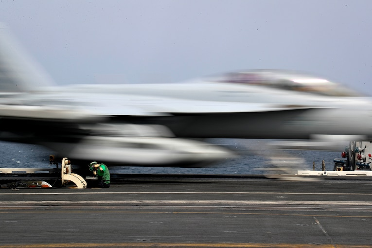 A fighter jet races past a sailor who is sitting and working on the flight deck of an aircraft carrier.