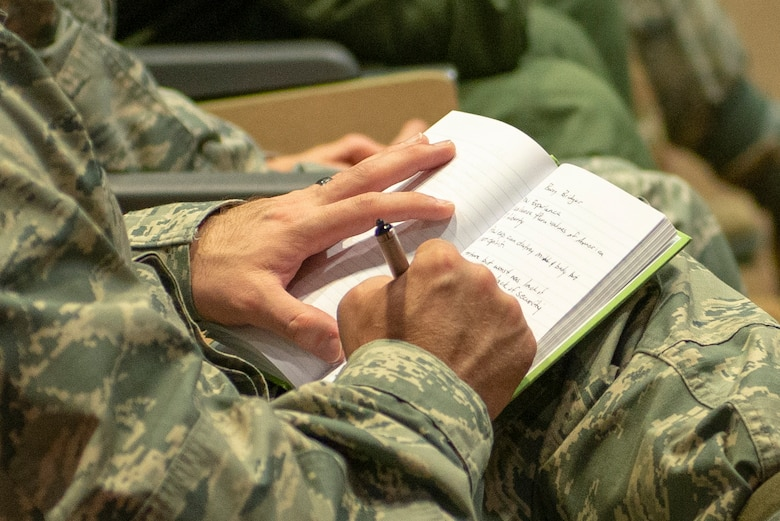 Team Offutt member takes notes during speech presented by retired Air Force Lt. Col Barry Bridger at the commander's updated briefing May 16, 2019, at Offutt Air Force Base, Nebraska. Bridger is a six-year survivor of Vietnam's Hoa Loa prisoner of war camp.