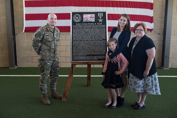 Col. Parks Hughes (left), Special Warfare Training Wing commander, present a plaque to the family of Senior Airman Bradley Smith, a fallen Special Tactic Airman and Silver Star recipient, during a dedication ceremony April 19 at Joint Base San Antonio-Lackland Medina Annex, Texas.