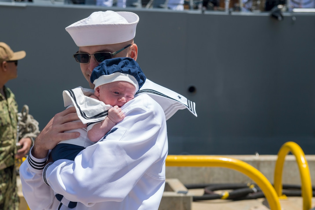 A sailor holds a small baby.