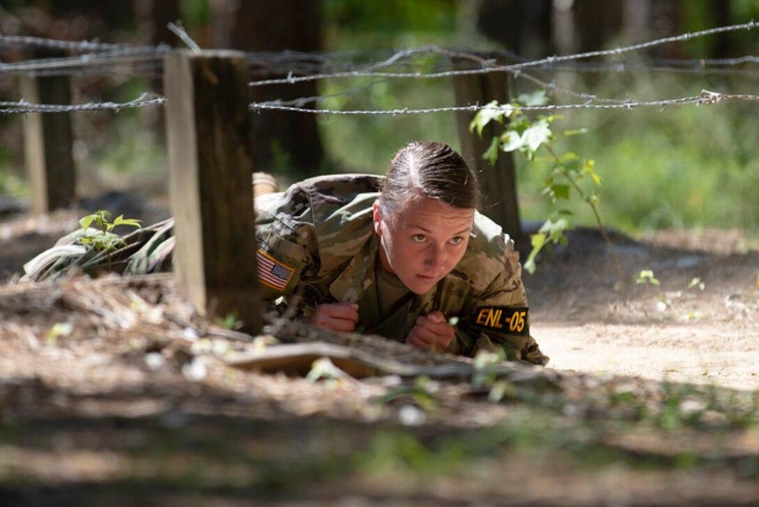 A soldier crawls under barbed wire.