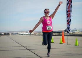 A runner strikes a pose as she crosses the finish line of the Run with History Half Marathon, 10k and 5k at Edwards Air Force Base, Calif., May 18. (U.S. Air Force photo by Giancarlo Casem)