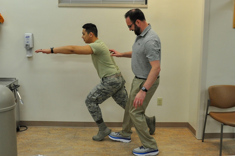 Dr. Jason Wheeler, 359th Medical Operations Squadron Physical Therapy Flight physical therapist, repositions the foot of Airman 1st Class Albert Lapera, 359th Medical Group physical therapy technician, as he does a sneaky lunge, an exercise used to help patients with balance. Arthritis Awareness Month, which is observed in May, is a time to motivate people, especially those with arthritis, to become more physically active.