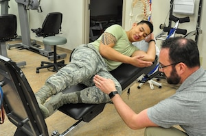 Airman 1st Class Albert Lapera, 359th Medical Group physical therapy technician, performs a single-legged squat on the total gym machine as Dr. Jason Wheeler, 359th Medical Operations Squadron Physical Therapy Flight physical therapist, instructs proper placement of his foot. Arthritis Awareness Month, which is observed in May, is a time to motivate people, especially those with arthritis, to become more physically active.
