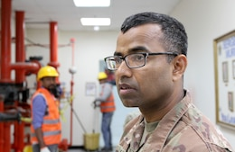 Staff Sgt. Zafar Iqbal, 184th Sustainment Command, observes maintence contractors at Camp Arifjan, Kuwait, Feb. 28, 2019.