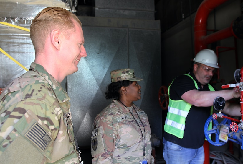 Sgt. 1st Class Michael Armstrong and Master Sgt. Deangelis Taylor, 184th Sustainment Command, observe a contractor working on pipes at Camp Arifjan, Kuwait, Feb. 28, 2019.