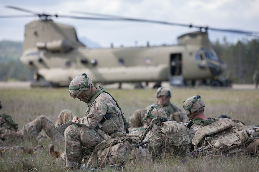 A group of soldiers in camouflage uniforms and helmets sits in the grass as a helicopter awaits in the distance.