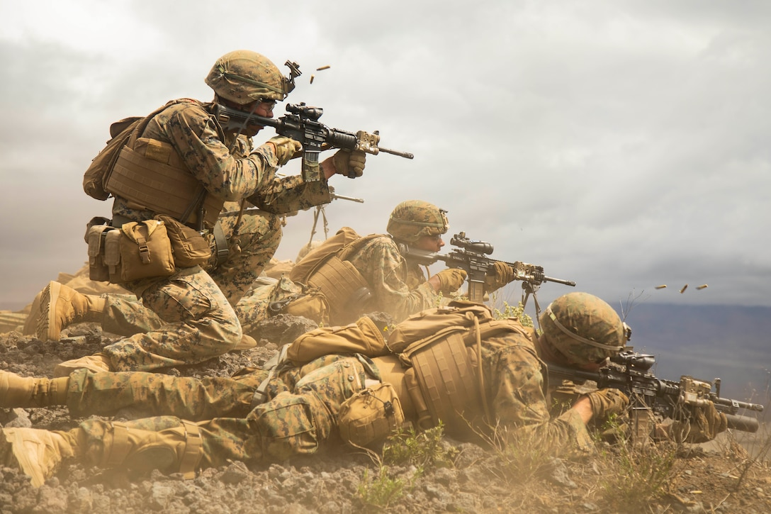 A Marine fire team fires rifles downrange from the ground.