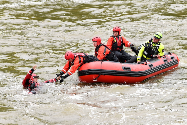 Airmen wearing vests, waders and helmets form a chain inside a raft to reach and rescue another airman in a river.
