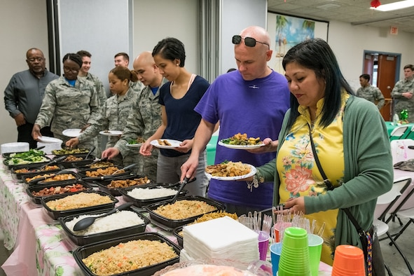 Team Dover members proceed through the food line at the Asian American Pacific Islander Heritage Month Luncheon May 17, 2019, in Base Chapel 2 at Dover Air Force Base, Del. A car wash and lumpia sale held by the AAPIHM committee raised enough funds to host the free luncheon, which was catered by a local Chinese restaurant. Over 80 Team Dover members attended the luncheon. (U.S. Air Force photo by Roland Balik)