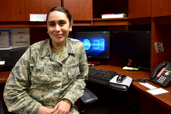 A woman wearing the Airman Battle Uniform sits at a desk.