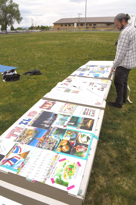 A visitor enjoys poster boards representing some of the many different country's celebrated during the Asian American Pacific Islander Heritage festival, held May 16 at the softball fields, Hill Air Force Base, Utah. The annual event is part of AAPI Heritage Month celebrating the cultural traditions, ancestry, native languages, and unique experiences represented among more than 50 ethnic groups speaking more than 100 languages from Asia and the Pacific Islands. (U.S Air Force photo by Todd Cromar)