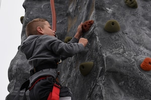 Keaton Evans, California Dreaming Spring Block Party attendee, climbs a rock wall May 18, 2019, at Travis Air Force Base, California. The 60th Air Mobility Wing chaplain's office hosts quarterly block parties to promote goodwill and camaraderie among Travis Airmen and their families. (U.S. Air Force photo by Airman 1st Class Cameron Otte)
