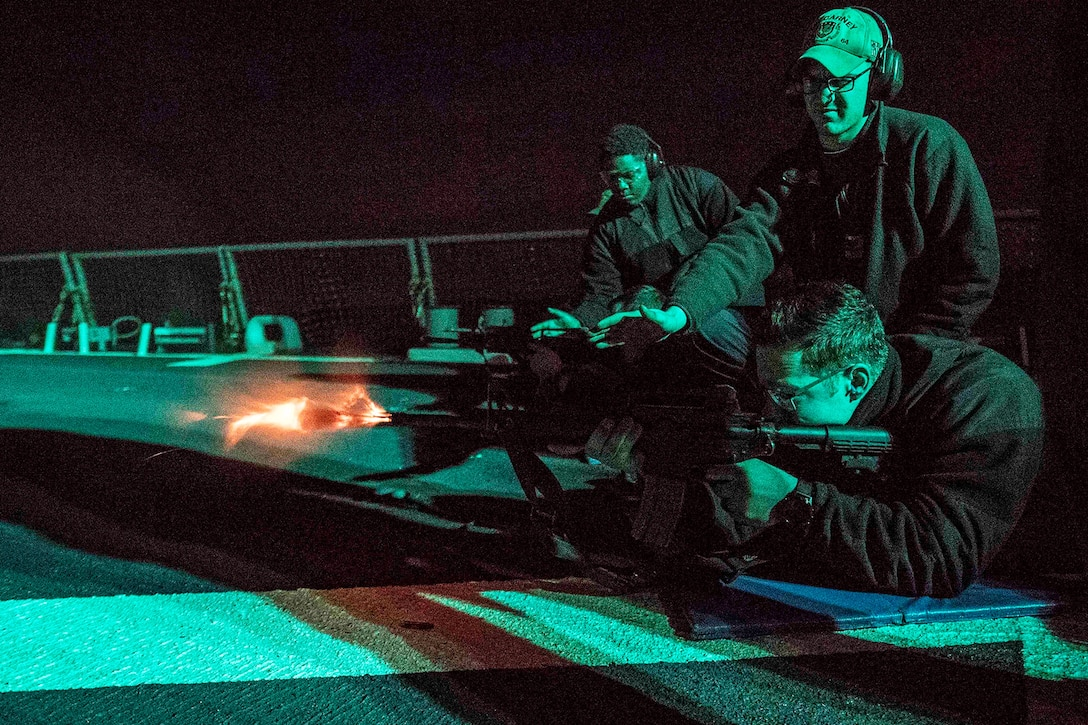 A sailor fires a weapon at night on a ship.