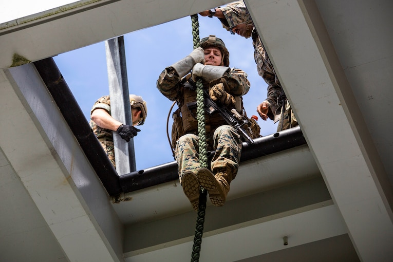 A Marine sits at the opening of a square hole holding a rope between his arms and legs.