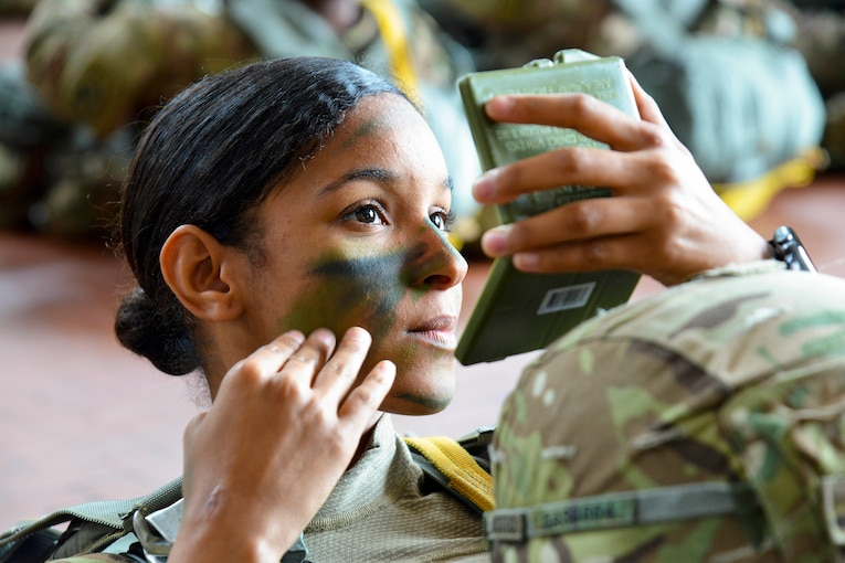 A soldier applies pant onto her face will looking at a compact mirror.