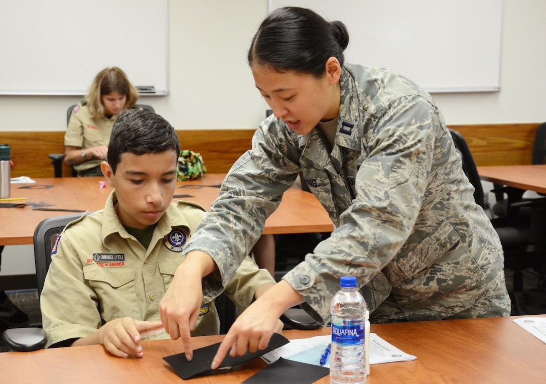 Capt. Pamela Zhang, a chemist with the Air Force Technical Applications Center, Patrick AFB, Fla., helps Emmanuel Lyttle, a Boy Scout with Troop #9 in Osceola, Fla., build a model cloud chamber April 13, 2019. Lyttle was one of 93 scouts – boys and girls – to visit the Department of Defense's sole nuclear treaty monitoring center to earn scouting's nuclear science merit badge.  Zhang was one of several AFTAC Airmen who volunteered their time to the event. (U.S. Air Force Photo by Susan A. Romano)