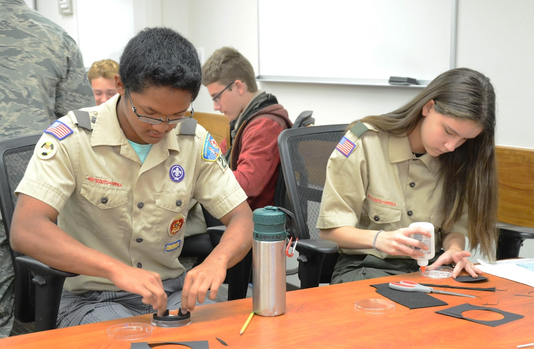Cody Reynoso (left) a 10th grader at Eau Gallie High School in Melbourne, Fla., and Emily Carta, a 10th grader at Edgewood Jr/Sr High School in Merritt Island, Fla., build a model cloud chamber during their visit to the Air Force Technical Applications Center, Patrick AFB, Fla., April 13, 2019.  The scouts came to the treaty monitoring center to earn their nuclear science merit badge with the help of AFTAC's scientists and engineers.  (U.S. Air Force Photo by Susan A. Romano)
