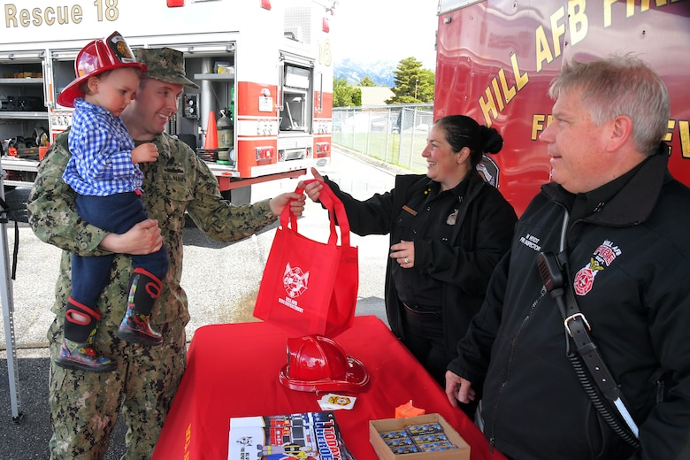 (left to right) Warren and Petty Officer 1st Class Gabe Burns, stop by to look at the Fire Trucks, and receive a child fire fighter helmet and other goodies from Tiana Bykowski and Wolfgang Heydt, both with 775 Civil Engineering Squadron, at the Wheels of Wonder event, May 17, 2019, Hill Air Force Base, Utah. (U.S. Air Force photo by Todd Cromar)