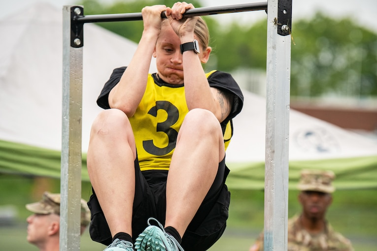 A soldier exhales while holding a chin-up bar and bringing her knees up.