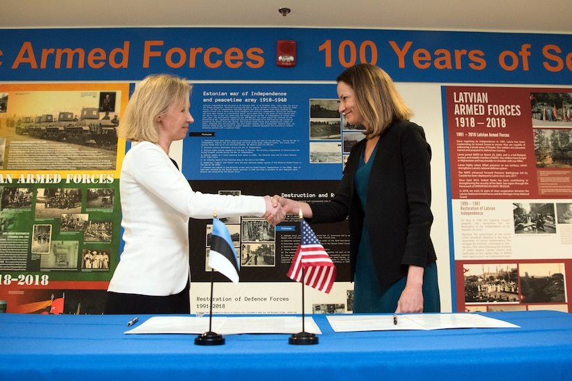 Defense leaders shake hands after signing agreement.