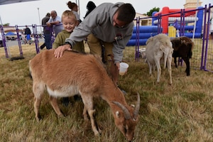U.S. Air Force Senior Airman Alexander Rivera, 821st Contingency Response Squadron Aerial Transportation Journeyman, and his son, Liam Rivera, pet a goat during the California Dreaming Spring Block Party May 18, 2019, at Travis Air Force Base, California. The 60th Air Mobility Wing chaplain's office hosts quarterly block parties to promote goodwill and camaraderie among Travis Airmen and their families. (U.S. Air Force photo by Airman 1st Class Cameron Otte)