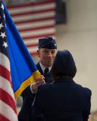 Col. Shannon Smith, incoming commander of the 124th Fighter Wing, hands the guidon to Chief Master Sgt. Kelly Bonjovi, Command Chief of the 124th FW, as he assumes command of the wing, May 5, 2019 at Gowen Field in Boise, Idaho.