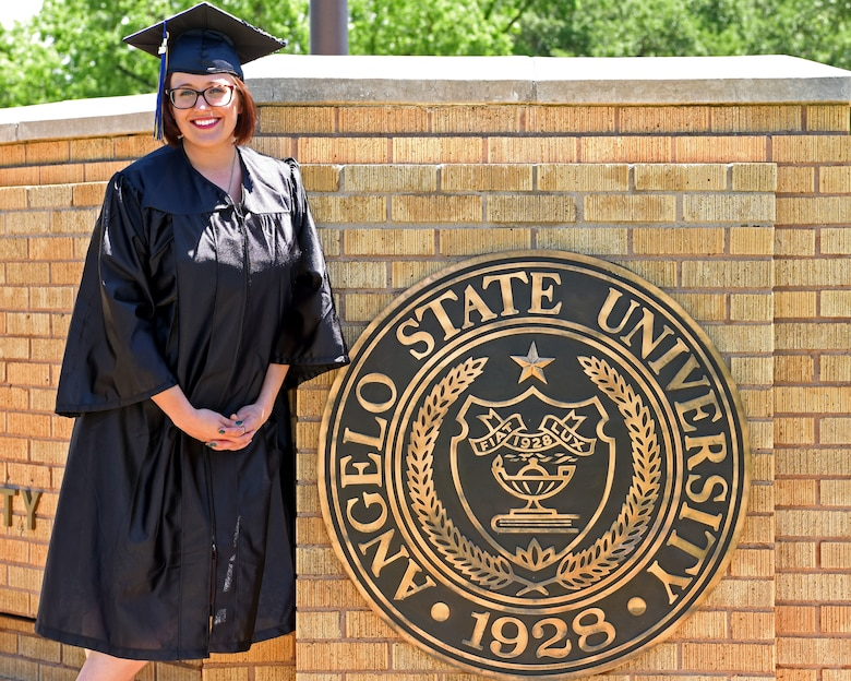 U.S. Air Force Staff Sgt. Britteny Griffith, a 316th Training Squadron linguist instructor at Goodfellow Air Force Base, stands in front of a sign at Angelo State University in San Angelo, Texas, May 8, 2019. Griffith recently graduated from ASU with a bachelor's degree in interdisciplinary studies. (U.S. Air Force photo by Airman 1st Class Ethan Sherwood/Released)