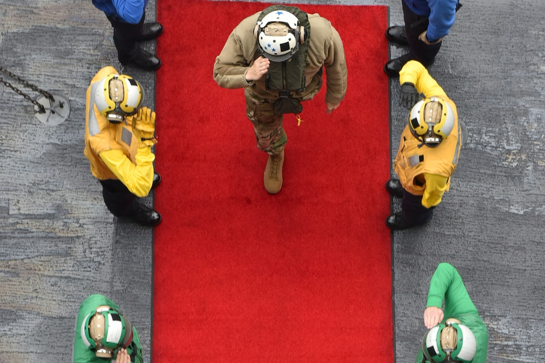 Two lines of sailors seen from above wearing colorful vests and helmets salute an officer as he walks on a red carpet.