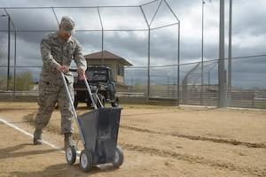 Staff Sgt. Juan Cimental, 341st Force Support Squadron sports program manager, lays down chalk markers on a softball field May 20, 2019, at Malmstrom Air Force Base, Mont.