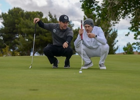U.S. Marshal Zack Tyler and Joey Gonzalez discussing putting strategy during a golf tournament during Police Week, at Edwards Air Force Base, California, May 14. Police Week is observed May 13-17. (U.S. Air Force photo by Giancarlo Casem)