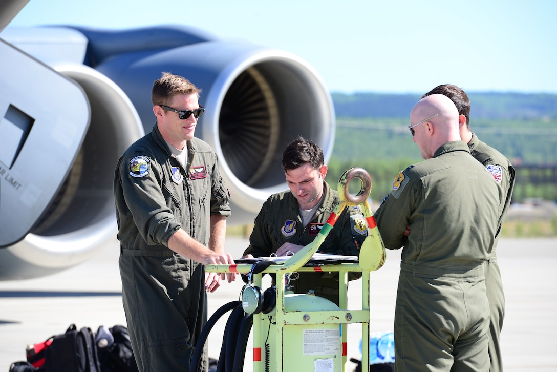 Four U.S. Air Force 909th Air Refueling Squadron Airmen discuss flight plans during exercise Northern Edge, May 16, 2019, at Eielson Air Force Base, Alaska.