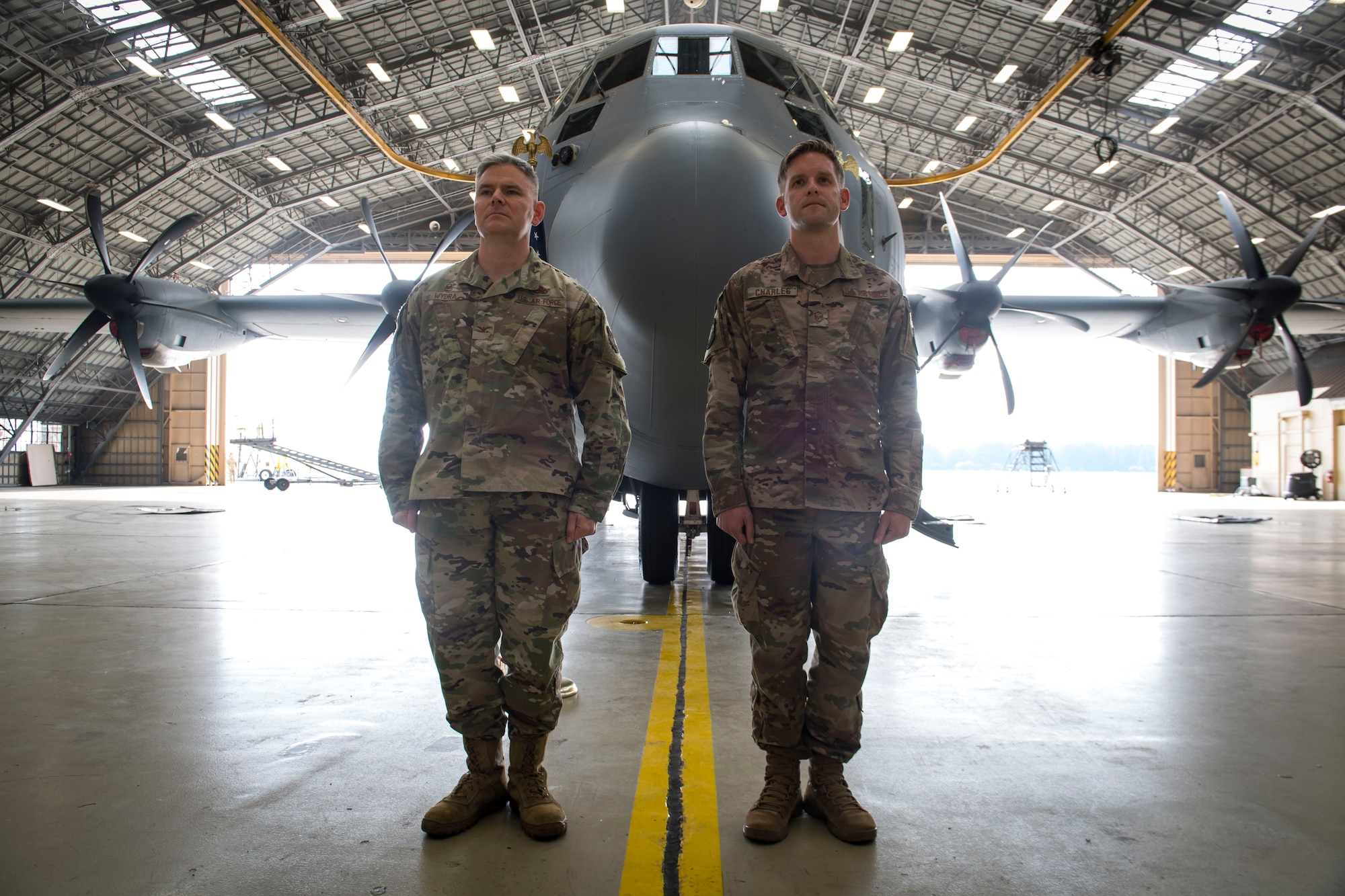 Col. Todd Wydra, 374th Maintenance Group commander (left), and Master Sgt. James Charles, 374th Aircraft Maintenance Squadron production superintendent, stand at attention
