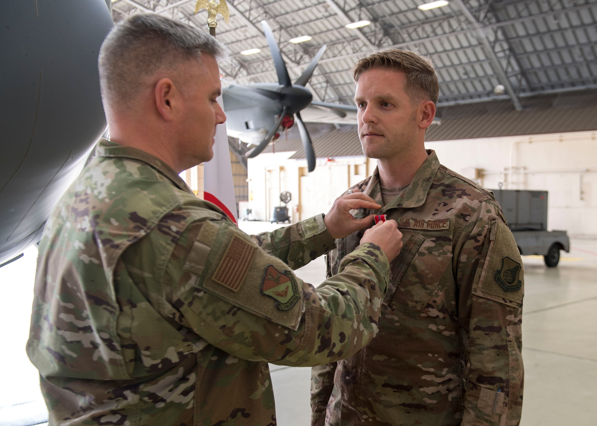 Col. Todd Wydra, 374th Maintenance Group commander, pins a Bronze Star Medal on Master Sgt. James Charles
