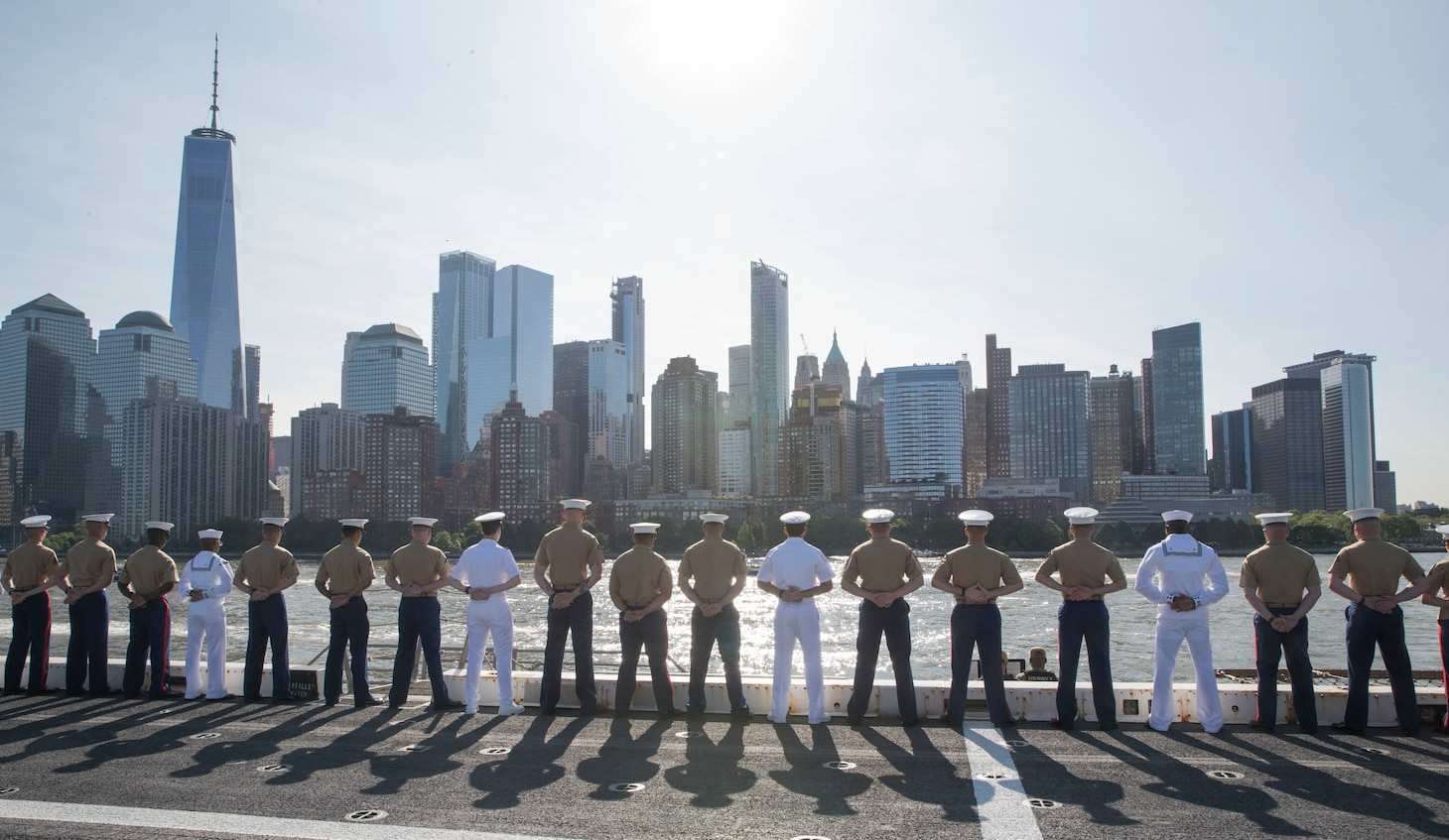 Sailors and Marines man the rails on the flight deck of the amphibious transport dock ship USS New York (LPD 21), as they approach New York City for Fleet Week New York.